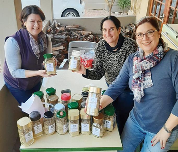 Saretha Conrade (links), Dalia Wilck (middel) en Lezelma Pretorius van die Oudtshoorn Rotariërs besig om die Jars of Hope met droë sopbestanddele te vul.